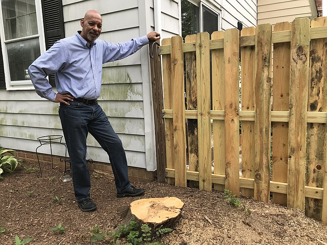 """Cory Laws, Housing and Neighborhood Improvement Coordinator for the Town of Herndon, stands where a large tree crashed through a homeowner's fence. He used resources established through his position to take care of the tree, fence and hopefully begin other repairs needed for the home. """"The big problem is resources, and I don't have any,"""" said Laws."""