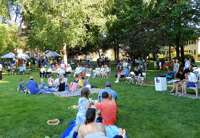 Friends and families picnic on the lawn of the Veterans Amphitheater.