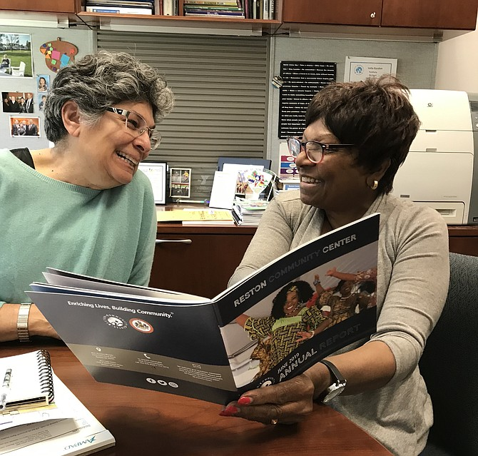 Reston Community Center Executive Director Leila Gordon and Chair of the Board of Governors Beverly Cosham review the June 2019 Annual Report.