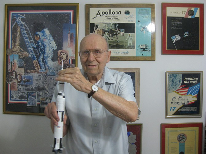 Great Falls resident Richard Cogan holds a model of the Saturn V rocket, which sent Apollo 11 on its way to the moon.