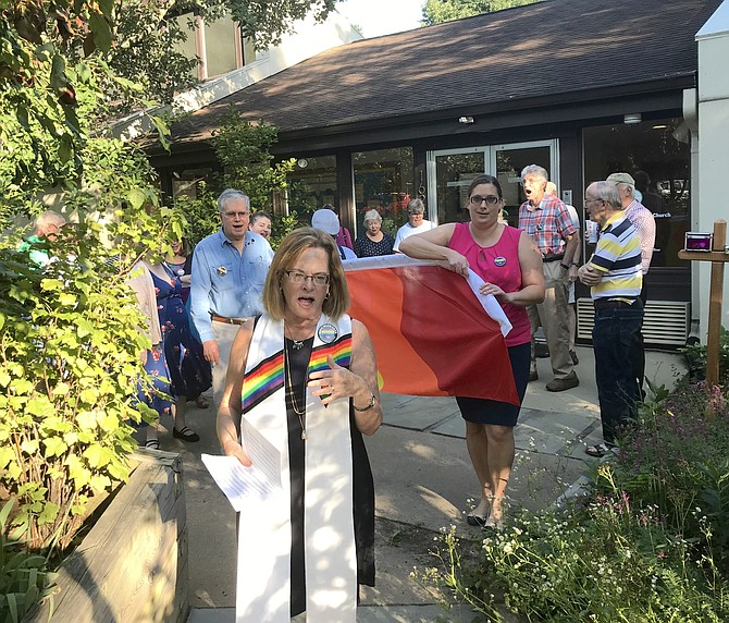 Rev. Dr. Debra W. Haffner, Minister United Universalist Church in Reston, leads church and community members toward the church's entrance off Wiehle Avenue, where they would install the church's new Rainbow flag.
