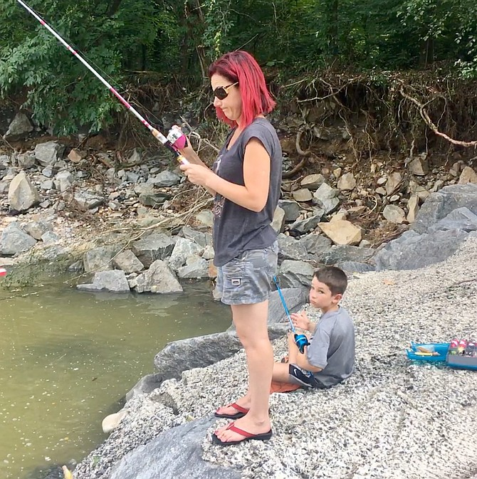 Lucas Yarushuk fishes with his mother on Four Mile Run. He used hot dogs as bait and said he had already caught a nice-sized eel and a fairly large fish. His mother said she would use the eel for Unani sushi.