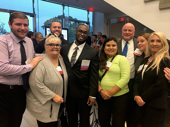 The staff of Everly-Wheatley Funeral Home celebrates with their colleague Anthony Wilson, a 2019 40 under 40 honoree, at a reception July 11 at United Way Worldwide headquarters.