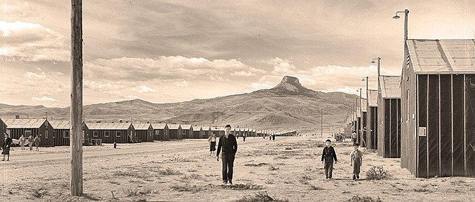 Japanese Americans travel between housing barracks with Heart Mountain on the horizon.