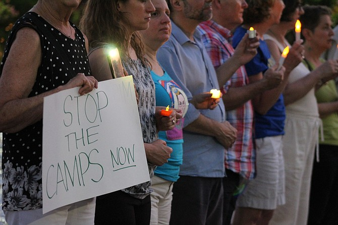Protestors hold candles and signs during a vigil at the Lights for Liberty event.