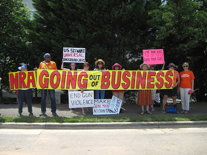 Grassroots activists hold a going out of business banner on the sidewalk across the road from the National Rifle Association in Fairfax during the July 14 protest against gun violence.