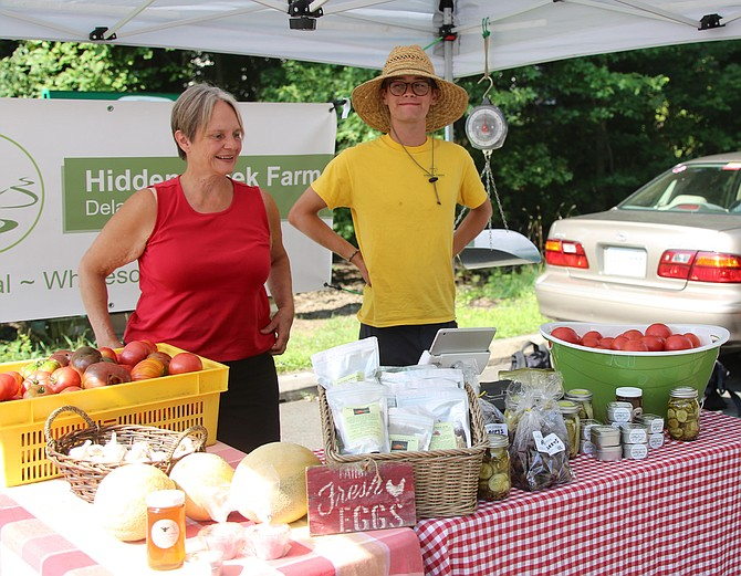 Owner of Hidden Creek Farm, Angela Young, and her intern Matt Zaremba, are greeting everyone who enters the market.