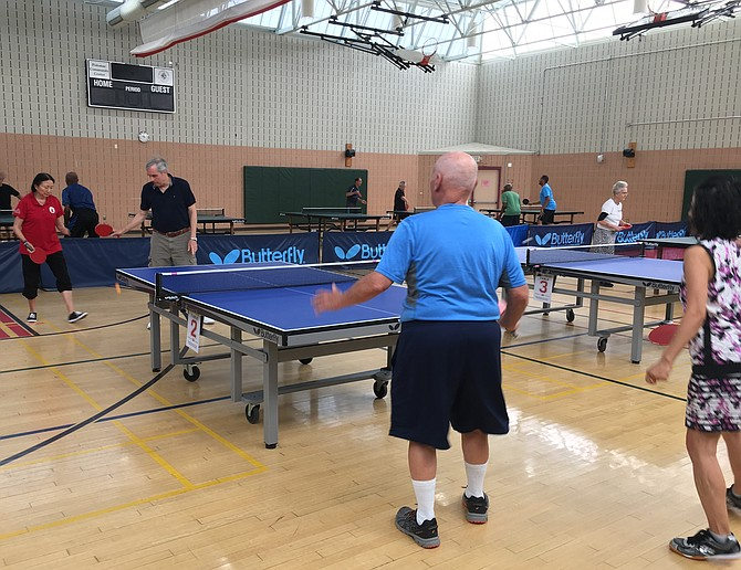 Pauline Jensen, top left, won gold in women's singles and women's doubles at the Maryland Senior Olympics Ping Pong Tournament at Potomac Community Recreation Center Saturday, July 27. Here she begins mixed doubles with partner Carl Bumiller playing Mi Kim and Richard Asendorf.