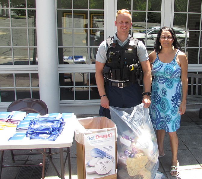 Alexandria Police officer Dylan Ignacio and volunteer Mary Luceri collect prescriptions at First Baptist Church on King Street.