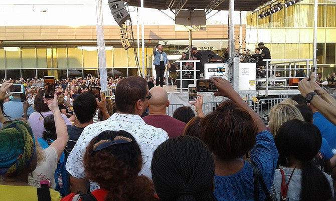 "Contemporary Christian music artist Danny Gokey points the microphone at his fans, who help him sing 2016 ballad ""Tell Your Heart to Beat Again"" at a free concert on a Friday evening July 26 outside Tysons Corner Center shopping mall."
