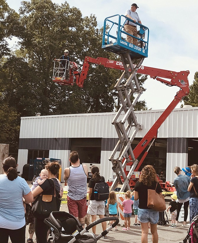 An RA Central Facilities Services staff member demonstrates how the slab scissor lift ascends to heights up to 25 feet during Totally Trucks held Friday, Aug. 2.