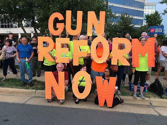 Hundreds of protestors gathered at NRA headquarters in Fairfax Monday, including members of Reston Herndon Indivisible holding these letters.