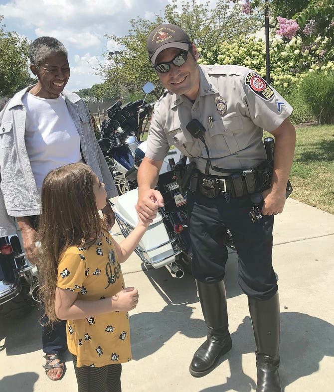 While Supervisor Cathy Hudgins (D-Hunter Mill) looks on, Amirah Khattak, 5, of Reston meets Officer R. B. Kitchens of the FCPD Motor Squad during the 2019 National Night Out celebration hosted by Hunters Woods Neighborhood Coalition and Cornerstones at Hunters Woods Plaza, on Tuesday, Aug. 6.