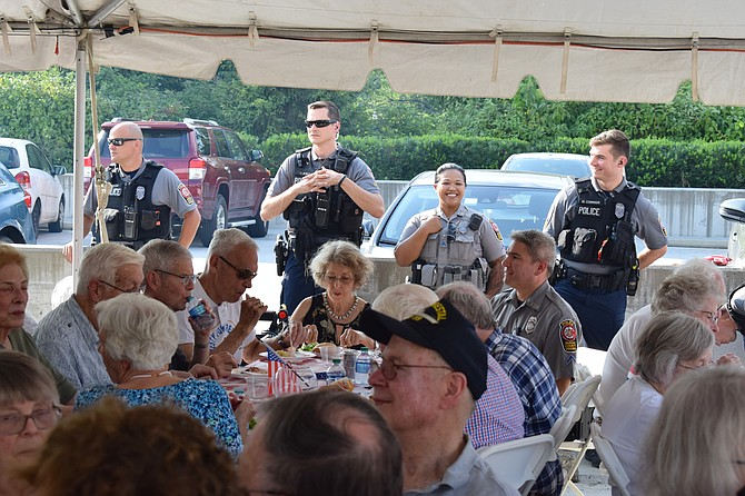 Fairfax County Police officers look on during remarks made at National Night Out. Vinson Hall hosts National Night Out as a way to say thanks to the many first responders who support the community every day.