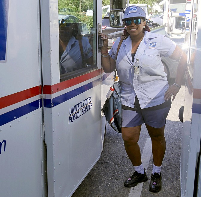 "Yvette ""E"" Stevens stands outside her mail delivery truck after her rescue of an elderly customer on her postal route who fell and lay on his kitchen floor for five days."