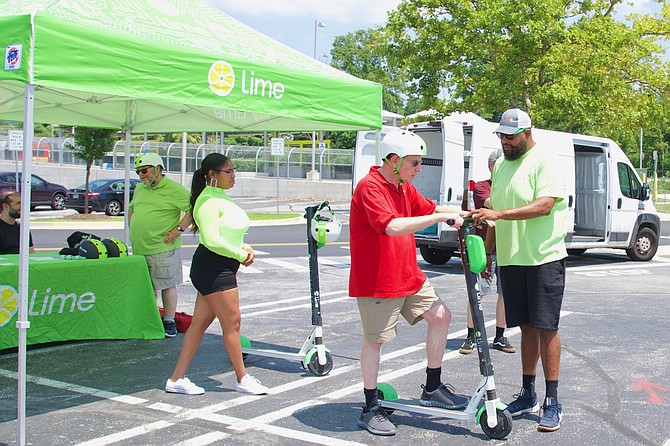 Chad Washington of Lime is instructing Neil Waldman how to operate an electric scooter Saturday, July 27 at the Montgomery County Democracy Boulevard transit site, right near Montgomery Mall.