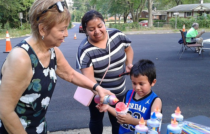 Fleur Noeth, left, adds the finishing touch to the snow cone of Santos Cruz, 5, right, while his mother, Belgica Cruz helps her son stay still for a brief moment Aug. 6 in Alexandria at the Bren Mar community block party during the 35th annual National Night Out.