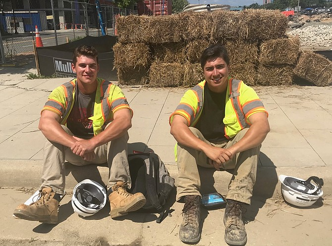 Virginia Tech rising seniors Liam Walter and Bobby Sherrill take a break from the heat while working at the Eisenhower Avenue Metro on July 24. The Eisenhower Avenue station is one of the six Metro stations south of Ronald Reagan Washington National Airport closed through Sept. 8 as part of WMATA's Platform Improvement Project.