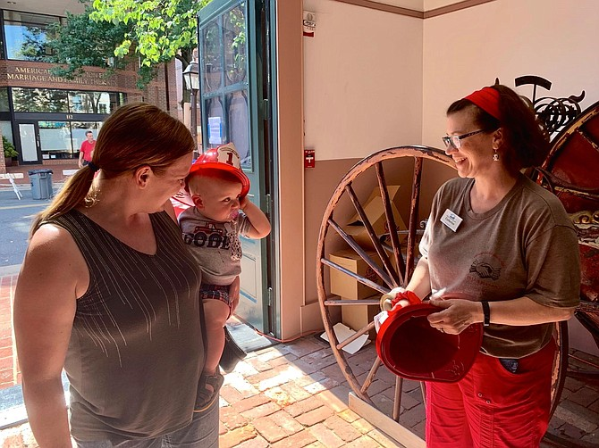 Corbin Meadows and mom Lindsay chat with volunteer Catherine Weinraub inside the historic Friendship Firehouse Museum.