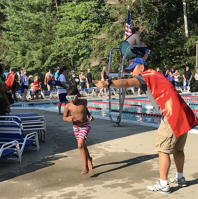 A young athlete charges across the Lake Audubon pool deck and towards the transition area during the 2nd annual Reston Youth Splash & Dash presented by CORE Foundation.