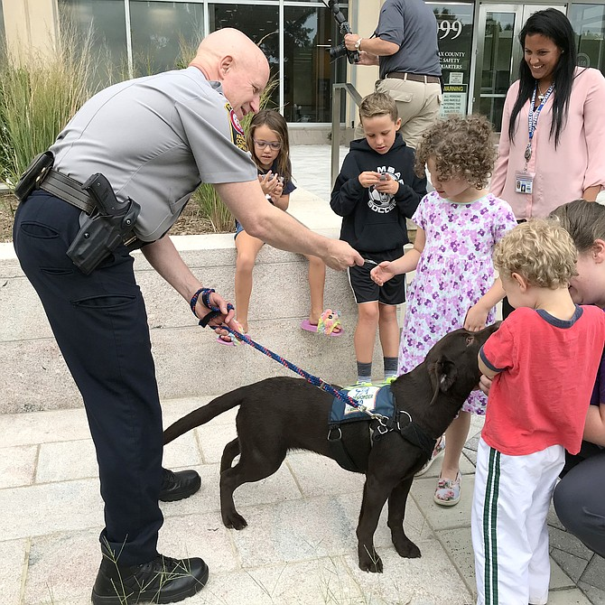 Children say hello to First Responder K9 Service Dog in Training Indy, and her handler Fairfax County Chief of Police Colonel Edwin C. Roessler Jr., during the department's Meet & Greet the Service Dogs.