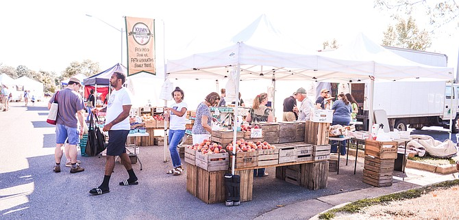 "Crowded with customers regular and new, the three produce stands that appear at the Lorton Farmers Market are filled with conversation and fresh produce. ""It is a smaller market so you get to know all of the vendors. We always interact with them."" says customer Curtis White."