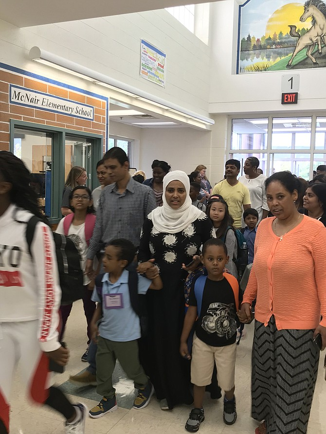 Hand in hand, family members and friends make their way to classrooms on the first day of the school year 2019-2020 at McNair Elementary in Herndon.