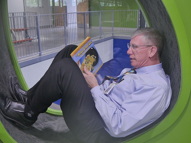 Jeff Chambers, director of Design and Construction for Arlington County Public Schools, demonstrates a reading nook in the second floor library.