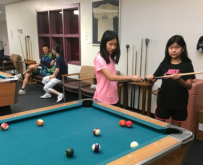 Amy Xu,13, left, and her sister Ellie, 9, practice pool at Potomac Community Recreation Center Friday.