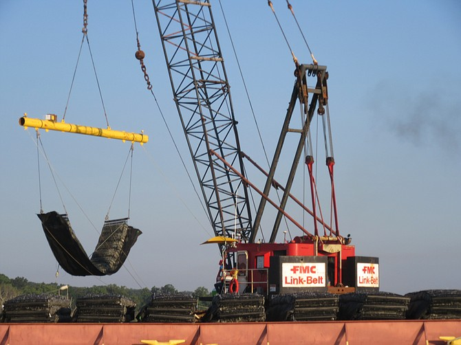 A crane lowers a marine mattress into the river to support the breakwater.