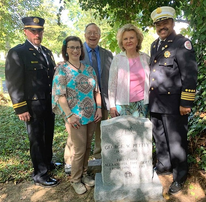 Acting Fire Chief Corey Smedley, right, poses for a photo with Captain Jason Kuehler, left, and Friendship Fire Engine Veterans Association Trustees Catherine Weinraub, Joe Shumard and Marion Moon at the newly unveiled gravestone of Fire Chief George Pettey Aug. 30 at Bethel Cemetery. Pettey died in the line of duty in 1911 and buried in an unmarked grave.
