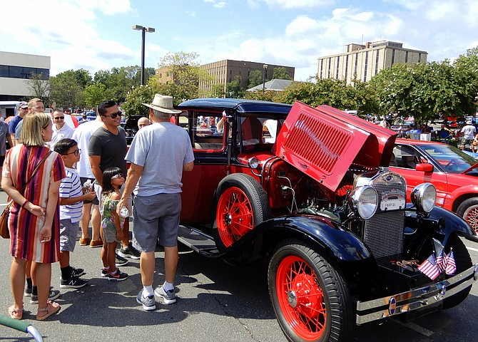 Benny Leonard (in hat) tells visitors how his 1930 Model A Ford coupe hauled bootleg liquor during Prohibition.