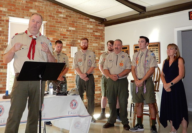 Scoutmaster Emeritus Kevin Gaughan speaks, while the Whalens, (from left) Ryan, Matt, Sean, Kevin, Connor and Patti, listen.