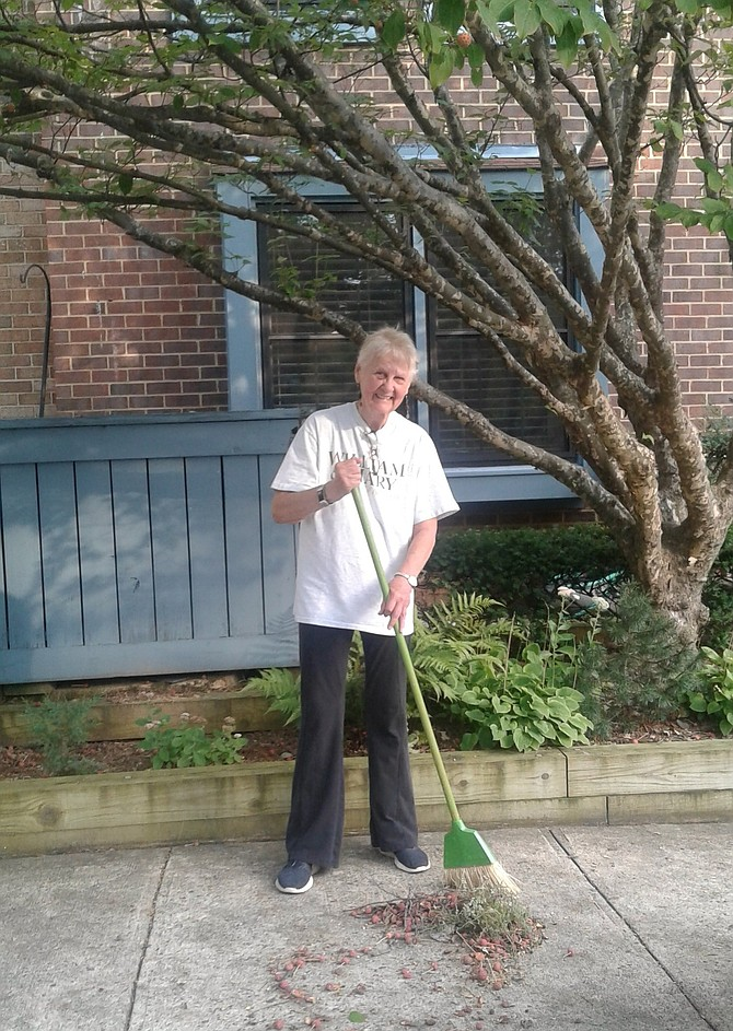 Rev. Dr. Kay Rodgers of Reston sweeps fruit that has dropped from her Japanese dogwood tree, so her neighbors and their pets don't step on the red berries and track them into their townhomes.  Although she completes this ordinary chore each fall, she finds it unusual that her tree drops its fruit in mid-August.