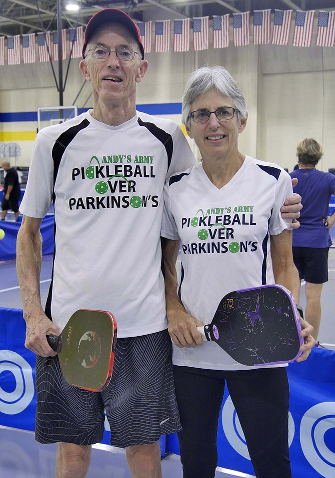 "Andrew Leighton and his wife, Helen White, pickleball partners, are sporting their ""Pickleball Over Parkinson's"" T-shirts."