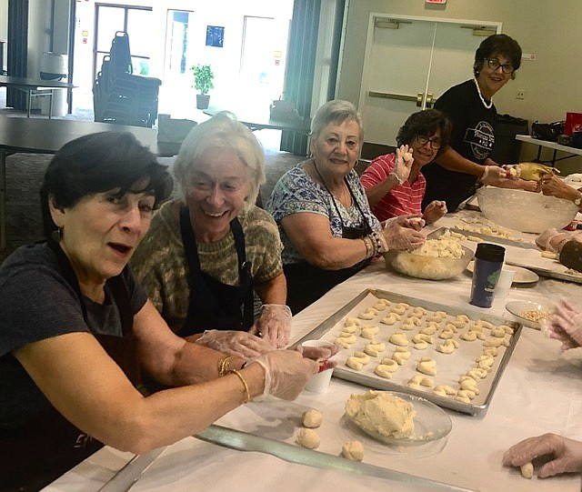 Church volunteers last year preparing bird's nests, ghrabee cookies, S-shaped.