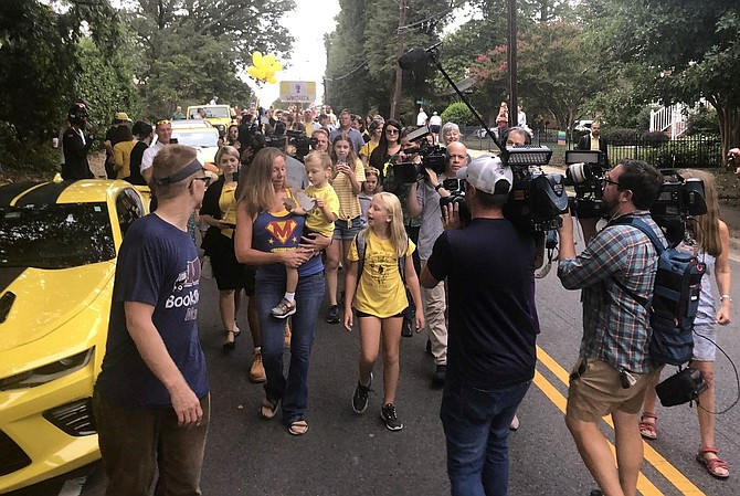 "Surrounded by media and well-wishers, Erin Weinburger holds son Whitaker, center, with daughter Lakeland as they walk to Charles Barrett Elementary School on Sept. 11. Whitaker, 4, who loves the yellow Bumblebee character in the ""Transformers,"" was greeted by more than 100 yellow vehicles in a surprise celebration of his first cancer-free birthday."