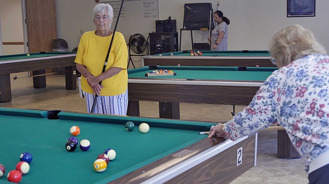 Diane Hill and Betty Roadcap face off in the 80s age division of 8-ball pool.