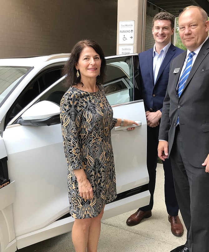 """Donald Davidson, Manager of Government Relations, Volkswagen Group of America (second from right), shows off the Audi-E-Tron with the first pure battery long-range car electromobility during the panel presentation, """"In a Word – Transportation!"""" hosted by the Dulles Regional Chamber of Commerce."""