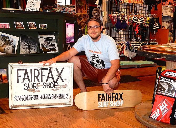 Adam Turrisi poses with the Fairfax Surf Shop's original sign.
