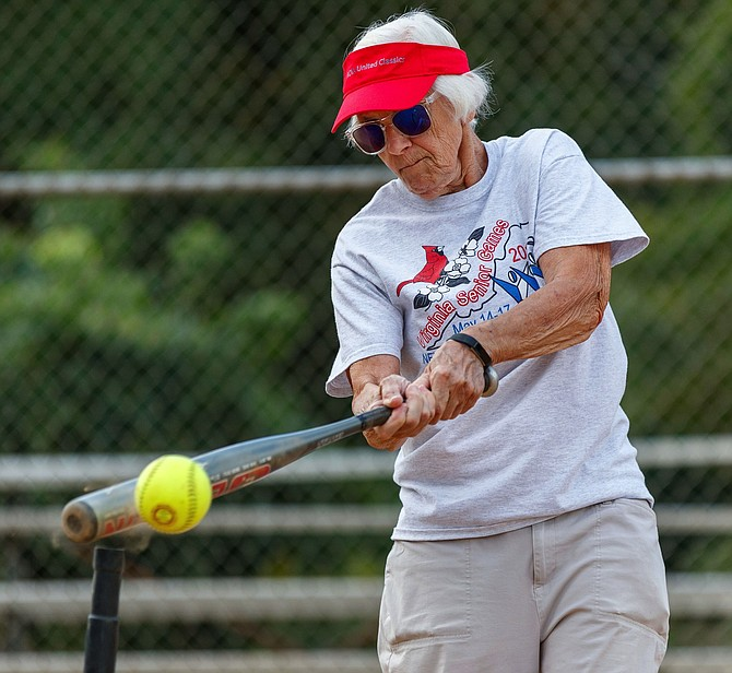 Falls Church resident Mary Lou D'Alessandris makes contact with the softball to win a gold medal in the 80-84 age group.