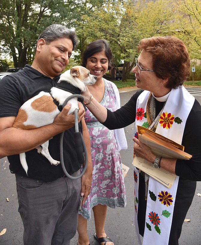 Rev. Meredith Heffner blessing Jay Dey, with Sam and Viji Dey, at the Blessing of the Animals at St. James Episcopal Church last weekend.