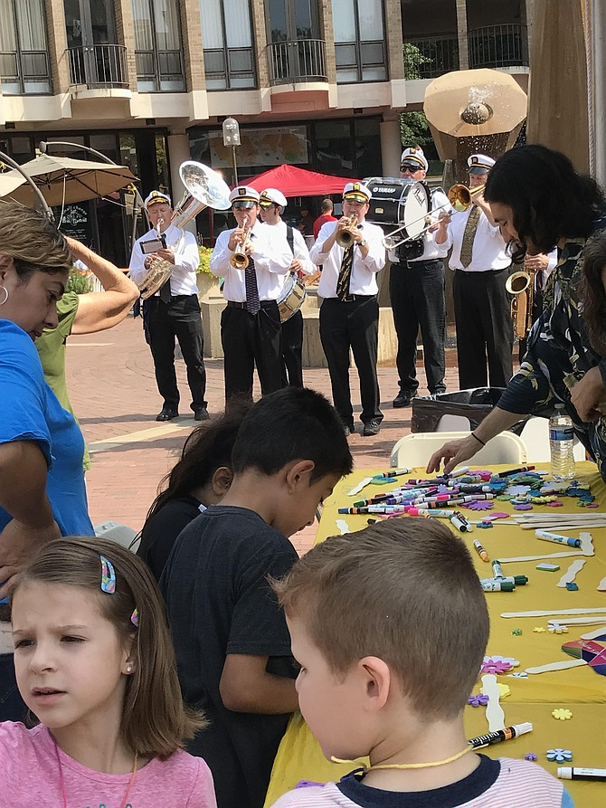 Children create art as the New Line Brass band goes New Orleans-style with a processional around the festival grounds, following the Welcome Ceremony and Naturalization Ceremony during the 2019 Reston Multicultural Festival.