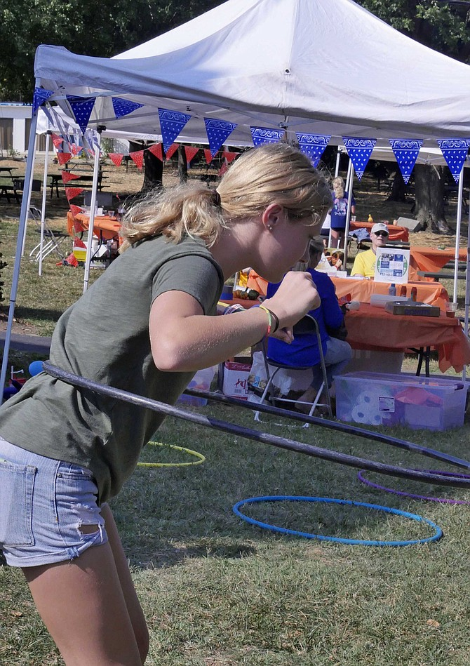 Elizabeth Schneider concentrates on keeping her hoop circling in the hula-hoop contest at BBQ, Boots and Bingo, Saturday, Sept. 28 at the Columbus Club of Arlington.