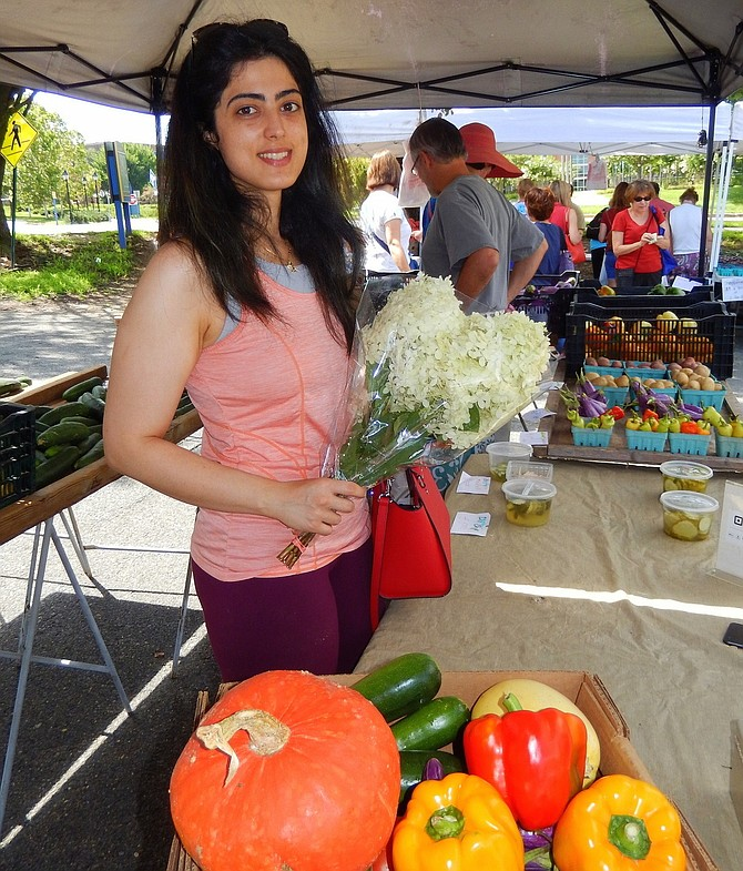 Sima Mahboubi is buying white hydrangeas, squash and bell peppers at the market.