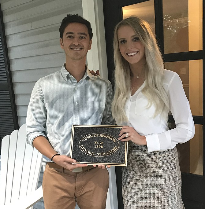 Spencer Ong and Caitlin Brown, owners of a residence deemed worthy by the Herndon Historic Society for inclusion in its Historic Homes Registry and Walking Tour Sites, hold the honorary plaque they will display beside the front door of their home located at 1017 Tyler Street.