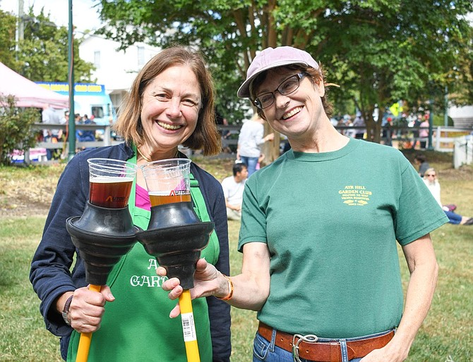 Nancy Moats and Christina Wren of Ayr Hill Garden Club use their free plungers given out by My Plumber as beer holders.