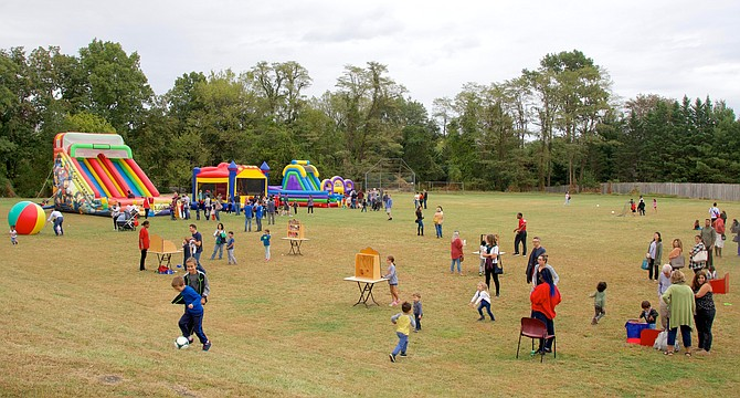 Children spread out over the Potomac Community Center fields enjoying inflatables and games.