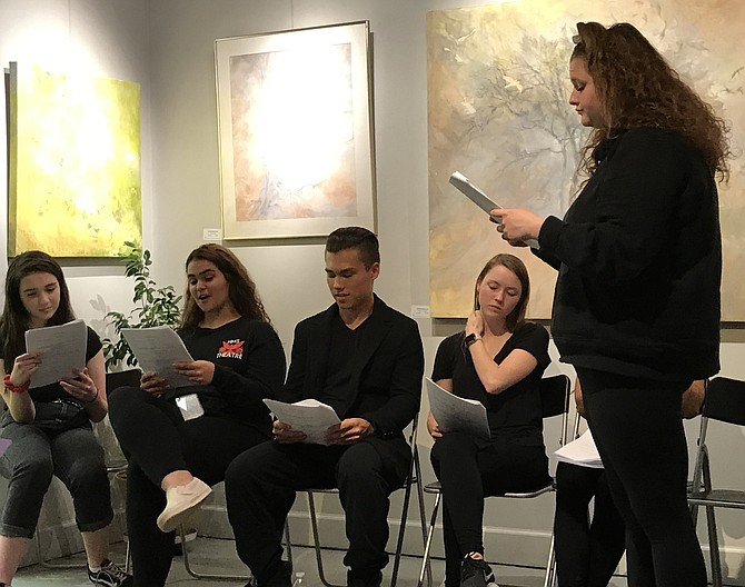 """Herndon High School Theatre presents """"Herndon Town"""" by Kristen LePine, a staged reading conceived and directed by Scott D. Parfumi and presented during Arts Week at ArtSpace. Cast member Meena Megahed of Reston reads her lines, as fellow HHS cast members Lulu Megahed, Isaiah Hagee, Bridget Neely and Kate Grover wait for their cues."""