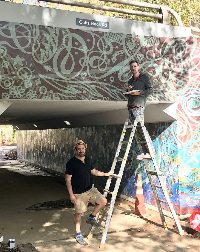 Artist Ben Volta talks with James Tafel Shuster as he paints panel edges to ensure color consistency of the massive Colts Neck Road Underpass mural in Reston.
